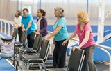 Image of older people exercising behind chairs