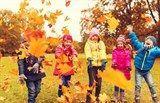 Five children playing in autumn leaves