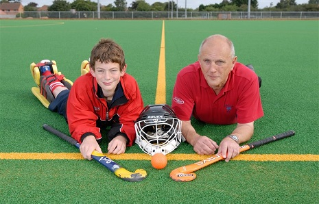 Hockey coach and child with hockey equipment
