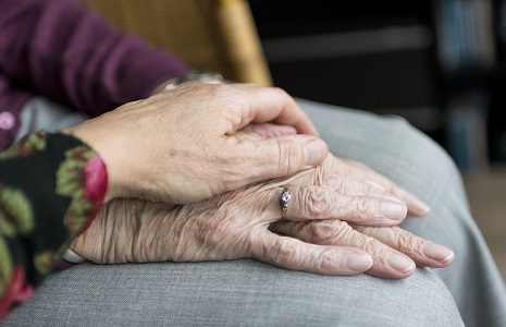 Two older people holding hands resting on lap